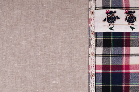 insertion: Fabrics background. Linen fabric, plaid flannel shirt with lace insertion, embroidery owl and wooden buttons.