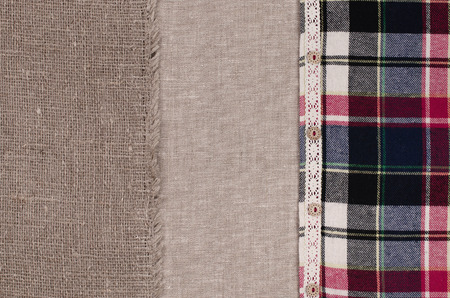 insertion: Fabrics background. Linen fabric, sackcloth, plaid flannel shirt with lace insertion and wooden buttons.