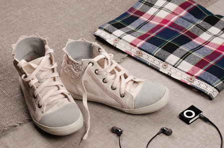 insertion: Clothing set. Womens sneakers and plaid shirt with lace insertion and black music player with headphones. Trendy lace insertion.