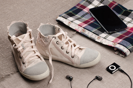 insertion: Clothing set. Womens sneakers and plaid shirt with lace insertion, tablet and black music player with headphones. Trendy lace insertion. Stock Photo