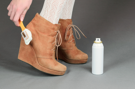 Female legs in brown suede boots on a gray background. Woman cleaning her suede shoes.