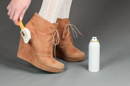 pantimedias: Piernas femeninas en botas de ante marrón sobre un fondo gris. Mujer que limpia sus zapatos de gamuza. Foto de archivo