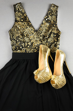 cinderella dress: Gold high-heeled shoes and black dress with gold accentson. Top view