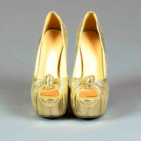 cinderella shoes: Gold high-heeled shoes on a gray background