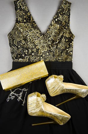 cinderella dress: Gold high-heeled shoes, clutch bag and black dress with gold accentson. Top view