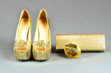 clutch bag: Gold high-heeled shoes, clutch bag and perfume on a gray background