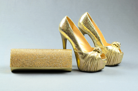 cinderella shoes: Gold high-heeled shoes and clutch bag on a gray background