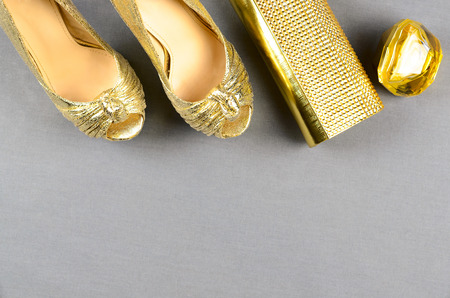 clutch bag: Gold high-heeled shoes, clutch bag and perfume on a gray background. Top view Stock Photo