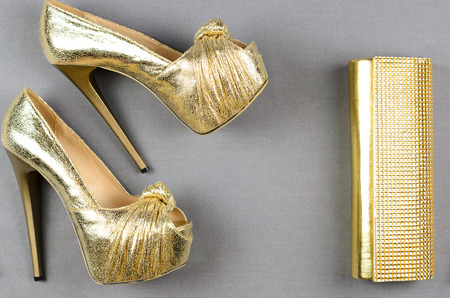 cinderella shoes: Gold high-heeled shoes and a clutch bag on a gray background. Top view