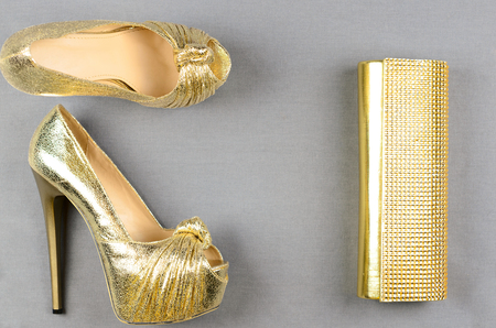 clutch bag: Gold high-heeled shoes and a clutch bag on a gray background. Top view