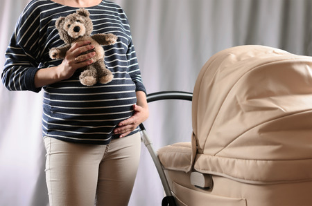 anticipation: In anticipation of motherhood. Pregnant woman standing near a pram and holding a toy bear on gray background
