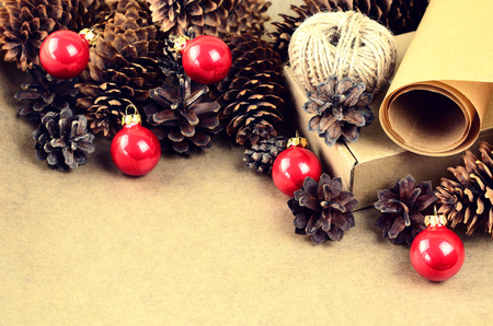 Natural materials for handcrafted Christmas decoration (paper, pine and spruce cones, jute, cardboard box) with red christmas balls