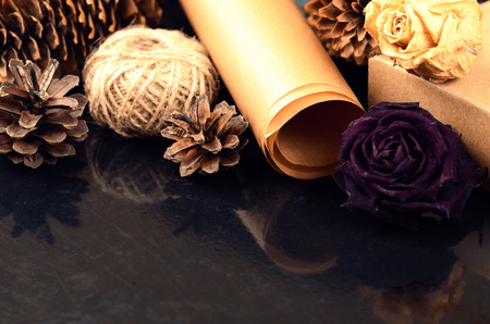 metier: Natural items collection for handcraft (paper, pine and spruce cones, jute, cardboard box, dried flowers) on dark surface