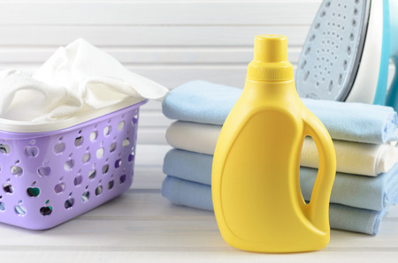 ironed: Dirty cloth in a plastic purple laundry basket, clean folded and ironed cloth, electric iron and blank yellow detergent bottle on white wood background