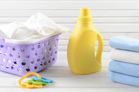 swaddling clothes: Dirty baby napkins in a plastic purple laundry basket, clean folded and ironed baby swaddle, baby toy and blank yellow detergent bottle on white wood background