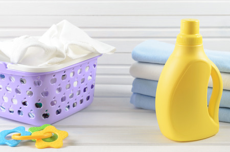 ironed: Dirty baby napkins in a plastic purple laundry basket, clean folded and ironed baby swaddle, baby toy and blank yellow detergent bottle on white wood background