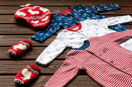 Baby boy clothes (sleepsuits, knitted hat and mittens) on brown wooden background Stock Photo