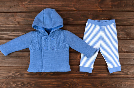 Babies blue knitted cardigan and striped pants on wooden background. Baby clothes Standard-Bild