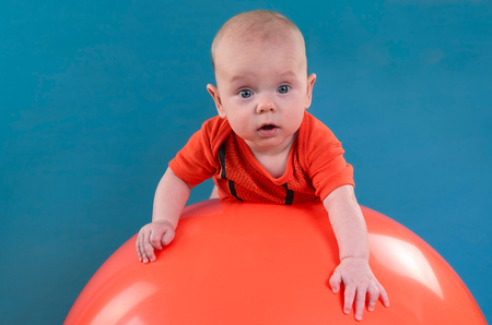 Cute baby lying on the orange fitball on the blue background. Concept of caring for the baby's health.