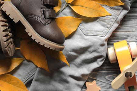 Fashion brown leather kids shoes, denim pants and accessories. autumn concept
