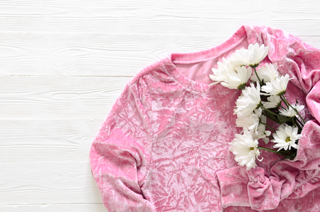 Womens fashion clothing (pink velvet sweater) and flowers on wooden background with copy space. Fashion concept. View from above, Flat lay. Spring summer collection