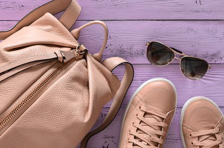 Das Zubehör und die Schuhe der Frauen (Lederrucksack und Turnschuhe, Sonnenbrille) auf violettem hölzernem Hintergrund. Frühlings-Sommerkollektion. Draufsicht, flach zu legen. Trendige Farben Standard-Bild - 93698447
