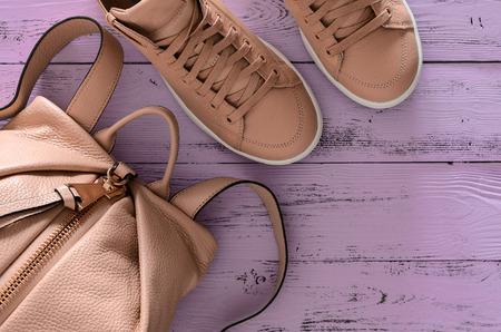 Mode-Accessoires und Schuhe der Frauen (Lederrucksack und Turnschuhe) auf violettem hölzernem Hintergrund. Frühlings-Sommerkollektion. Draufsicht, flach zu legen. Trendige Farben Standard-Bild - 93698465