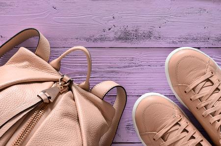 Mode-Accessoires und Schuhe der Frauen (Lederrucksack und Turnschuhe) auf violettem hölzernem Hintergrund. Frühlings-Sommerkollektion. Draufsicht, flach zu legen. Trendige Farben Standard-Bild - 93692261