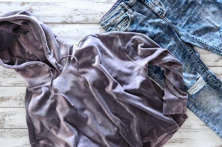 Die Kleidung der Frauen (violetter Samt Hoodie, Säure gewaschene Jeans) auf hölzernem Hintergrund. Outfit für Jugendliche. Draufsicht, flach zu legen. Trendige Farben Standard-Bild - 94220759