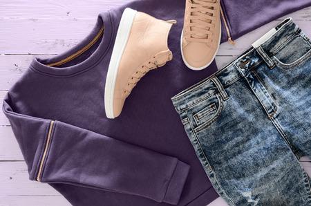 Die Kleidung der Frauen, Schuhe (violettes Sweatshirt, Säure wusch Jeans, lederne Turnschuhe) auf hölzernem Hintergrund. Outfit für Jugendliche. Draufsicht, flach zu legen. Trendige Farben. Standard-Bild - 94234140