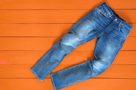 Blue mens jeans denim pants on orange background. Contrast saturated color. Fashion clothing concept. View from above Standard-Bild - 95165304