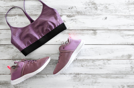 Womens sport bra and sneakers on wooden background with copy space. Active running (walking) footwear Standard-Bild - 95995915