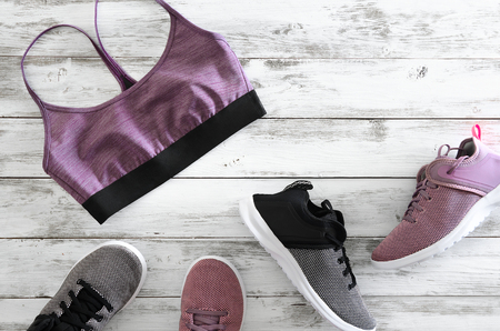 Womens sport bra and two pairs of sneakers (violet, black and white)  on wooden background with copy space. Active running (walking) footwear Standard-Bild - 96049285