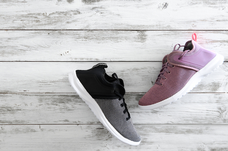 Sneakers (violet, black and white)  on wooden background with copy space. Active running (walking) footwear Standard-Bild - 96106524