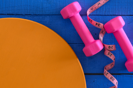 Dumbbells and tape measure on wooden background with copy space. Saturated colors (blue, orange, pink). Sport equipment. Active, healthy lifestyle concept Standard-Bild - 96083487
