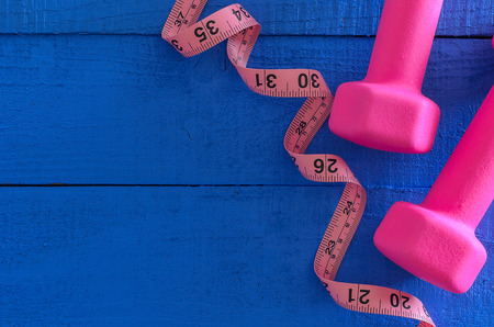Dumbbells and tape measure on wooden background with copy space. Saturated colors (blue, pink). Sport equipment. Active, healthy lifestyle concept Standard-Bild - 95995917