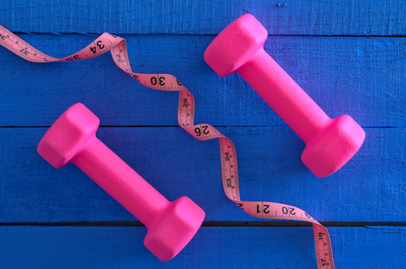 Dumbbells and tape measure on wooden background. Saturated colors (blue, pink). Sport equipment. Active, healthy lifestyle concept