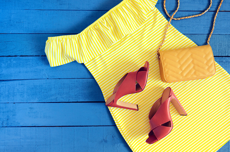 Womens clothing, accessories, footwear (yellow dress,  leather terracotta heel shoes,  crossbody bag). Fashion outfit. Shopping concept. Flat lay. Trendy, saturated colors. Spring summer collection