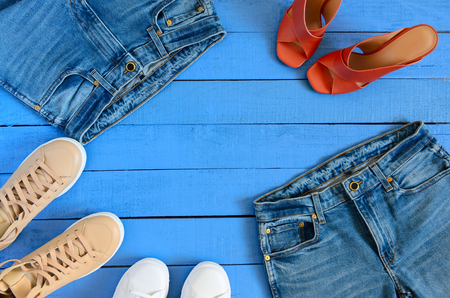 Womens clothing, footwear (blue jeans,  leather terracotta heel shoes,  nude sneakers). Fashion outfit. Shopping concept. Flat lay. Trendy, saturated colors. Spring summer collection Standard-Bild - 99635696