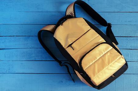 yellow golden backpack on blue wooden background Standard-Bild - 97468092
