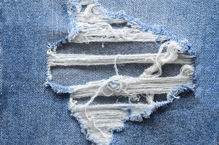 Jeans in wash blue with rip. Denim background, texture. Ripped destructed detail, close up. Standard-Bild - 97678732
