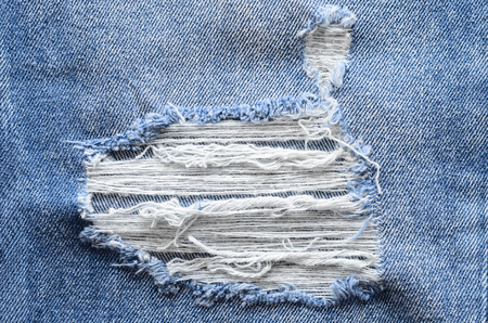 Jeans in wash blue with rip. Denim background, texture. Ripped destructed detail, close up. Standard-Bild - 97537256