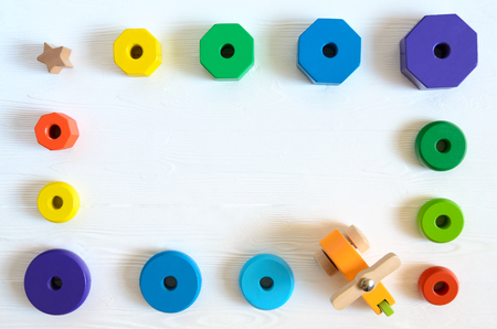 Learning developmental kids toys.  Shape sorter, geometric stacker, organic wooden baby toys. Flat lay, top view. Copy space Standard-Bild - 97600641