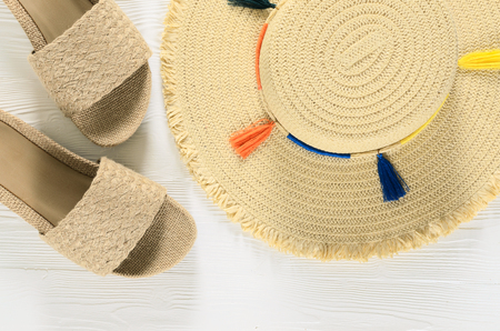 Womens summer accessories (straw hat and sandals) on white wooden background with copy space. Fashion beach travel concept. Flat lay Standard-Bild - 98423588