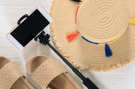 Womens summer accessories and sandals (straw hat, cellphone, selfie stick, flip flops) on white wooden background. Fashion look, travel concept. Flat lay. Natural organic stuff Standard-Bild - 98356033