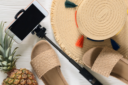 Womens summer accessories (straw hat, cellphone, selfie stick), pineapple on white wooden background. Fashion look, travel and summer concept. Flat lay. Natural organic stuff Standard-Bild - 98381328