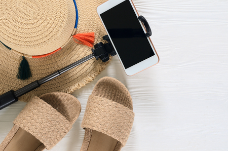 Womens summer accessories and sandals (straw hat, cellphone, selfie stick, flip flops) on white wooden background. Fashion look, travel concept. Flat lay. Natural organic stuff Standard-Bild - 98380180