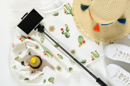 Set of womens clothing, accessories ( white cactus graphic pullover, straw hat, sneakers, cellphone, selfie stick) and live cactus on wooden background. Fashion outfit. Shopping, travel concept. Flat lay. Spring summer collection Standard-Bild - 98413336