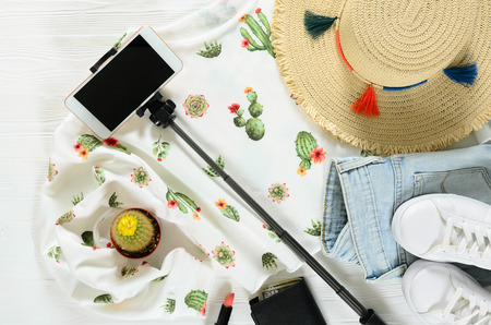 Set of womens clothing, accessories ( white cactus graphic pullover, straw hat, sneakers, jeans, cellphone, selfie stick, lipstick, wallet) and live cactus on wooden background. Fashion outfit. Shopping, travel concept. Flat lay. Spring summer collection Standard-Bild - 98408040