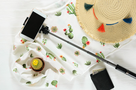 Set of womens clothing; accessories ( white cactus graphic pullover; straw hat; cellphone; selfie stick; wallet) and live cactus on wooden background. Fashion outfit. Shopping; travel concept. Flat lay. Spring summer collection Standard-Bild - 98431293